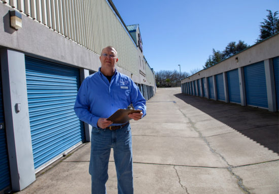 Service representative holding clipboard in front of blue storage containers